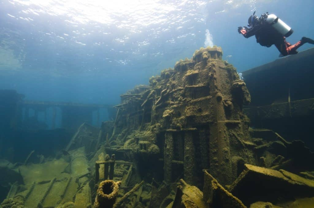 A NOAA archaeologist swims by the gigantic diesel engine of the steel freighter Nordmeer that lies in 40 feet of water within the Thunder Bay National Marine Sanctuary. Photo by Tane Casserley, NOAA Thunder Bay National Marine Sanctuary - Awesome Mitten - MittenTrip