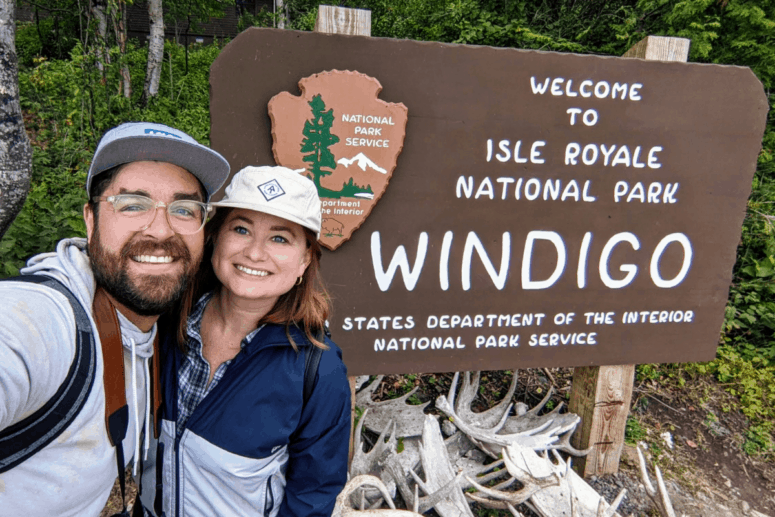 Nina and Jared in front of the Isle Royale National Park sign.